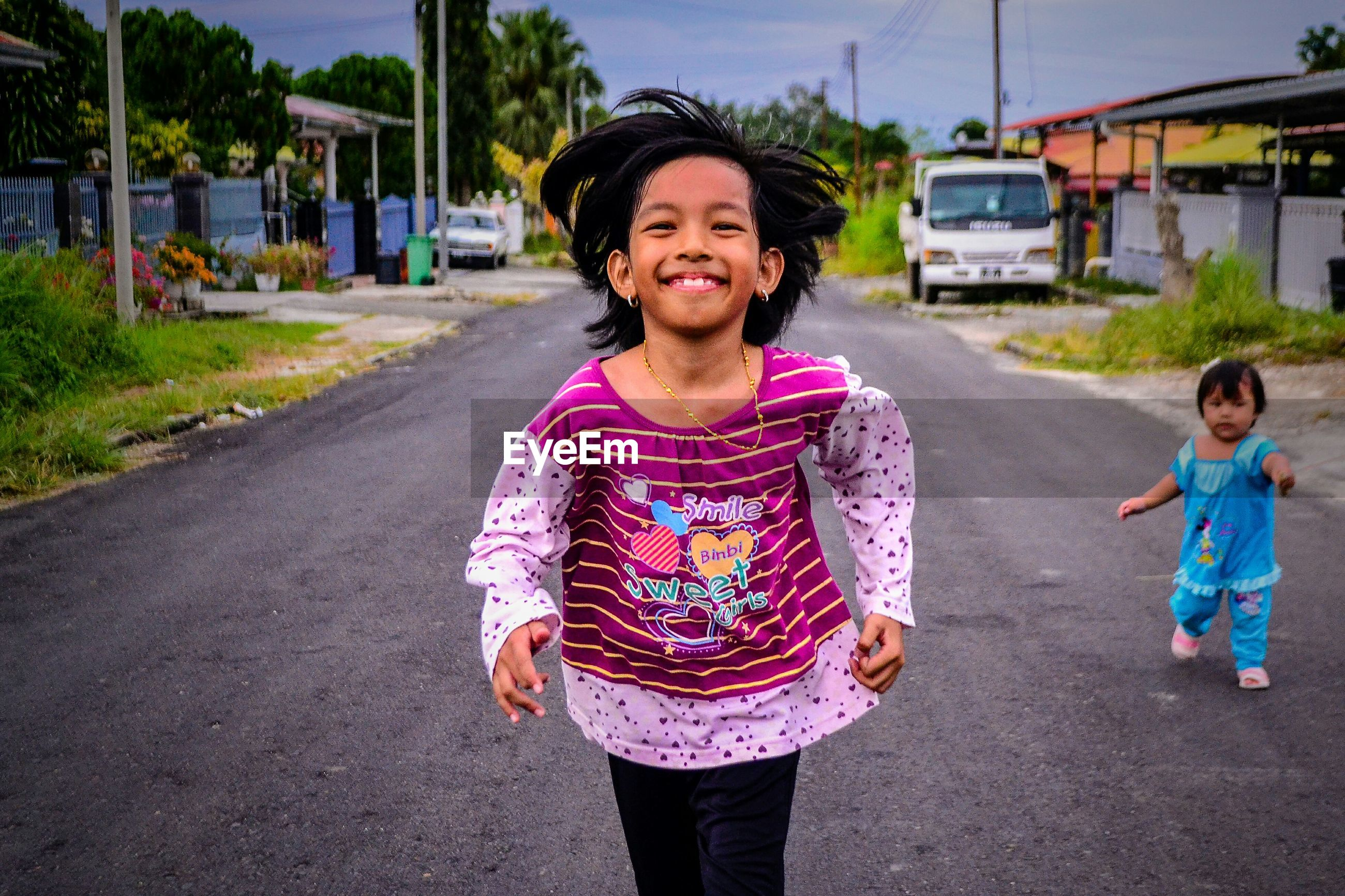 PORTRAIT OF A SMILING GIRL WITH ROAD