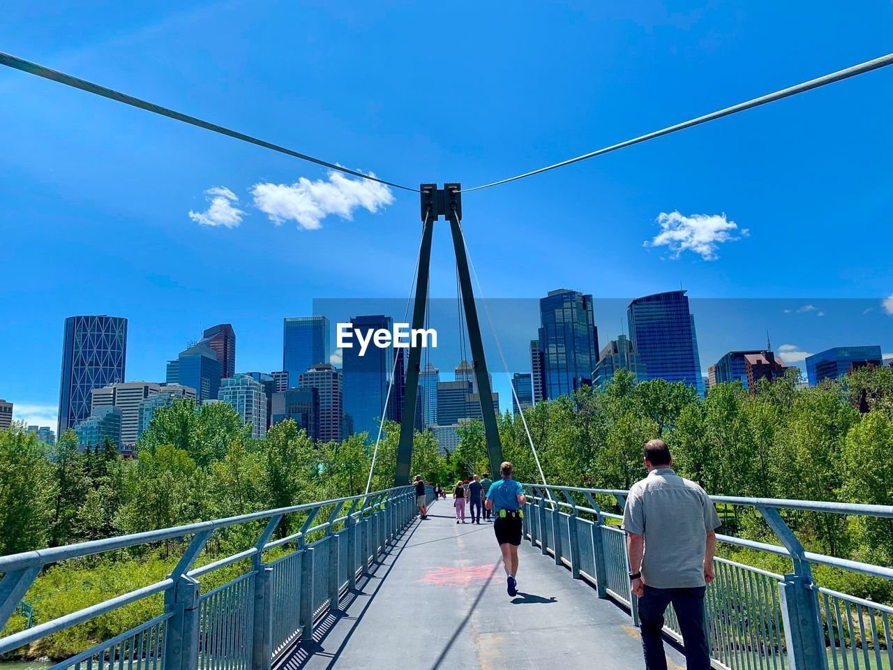 architecture, built structure, sky, city, building exterior, railing, day, bridge, walking, office building exterior, bridge - man made structure, nature, skyscraper, transportation, real people, cloud - sky, connection, city life, men, incidental people, tall - high, outdoors, cityscape