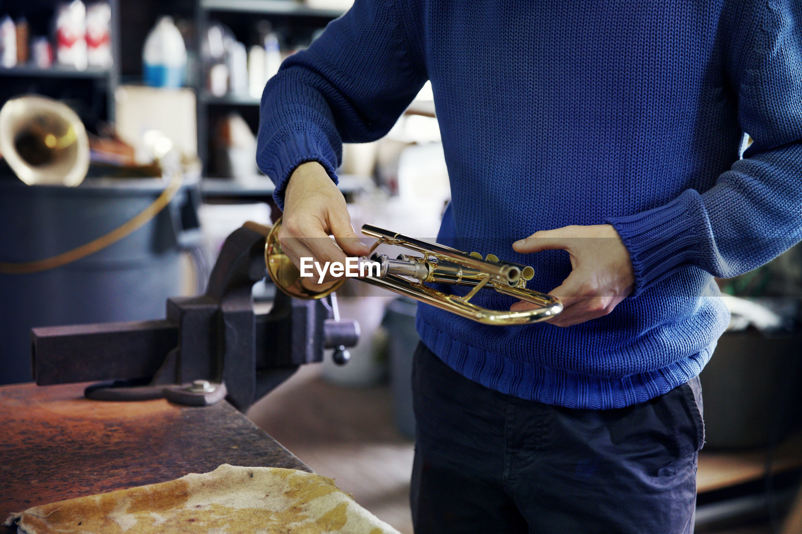 Midsection of man repairing trumpet