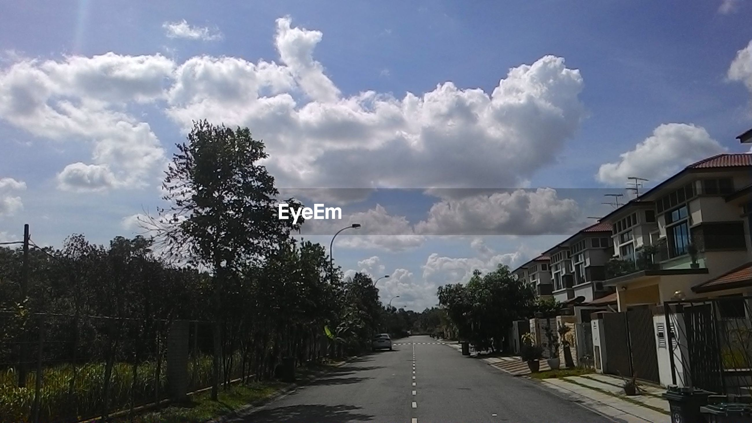 Road by buildings against cloudy sky