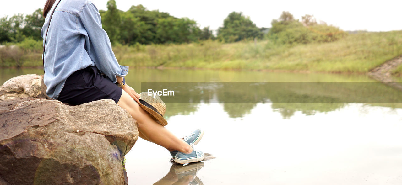 one person, solid, real people, lake, rock - object, water, rock, lifestyles, leisure activity, nature, sitting, day, casual clothing, focus on foreground, plant, tree, side view, beauty in nature, outdoors