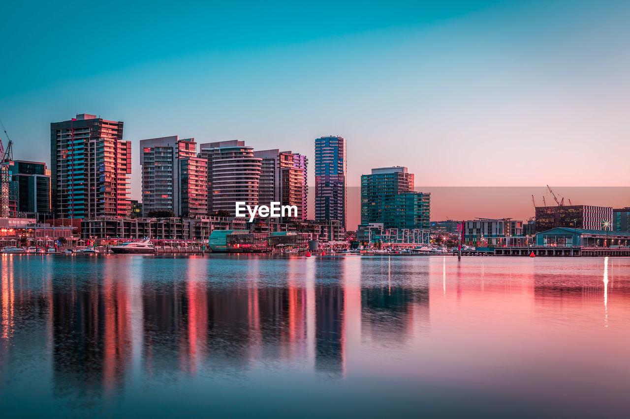 Illuminated City By Sea Against Clear Sky