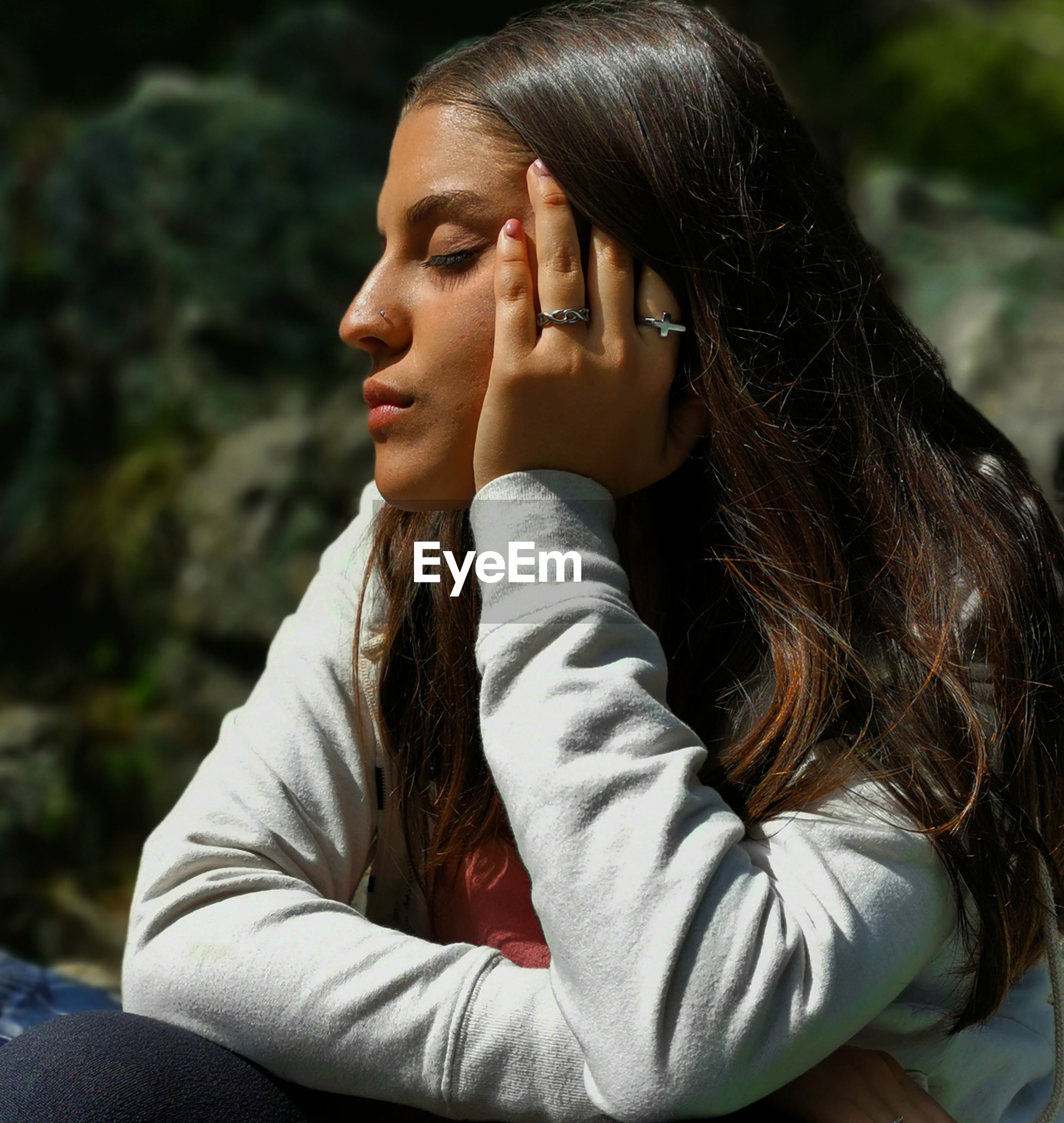 Young woman with eyes closed sitting outdoors