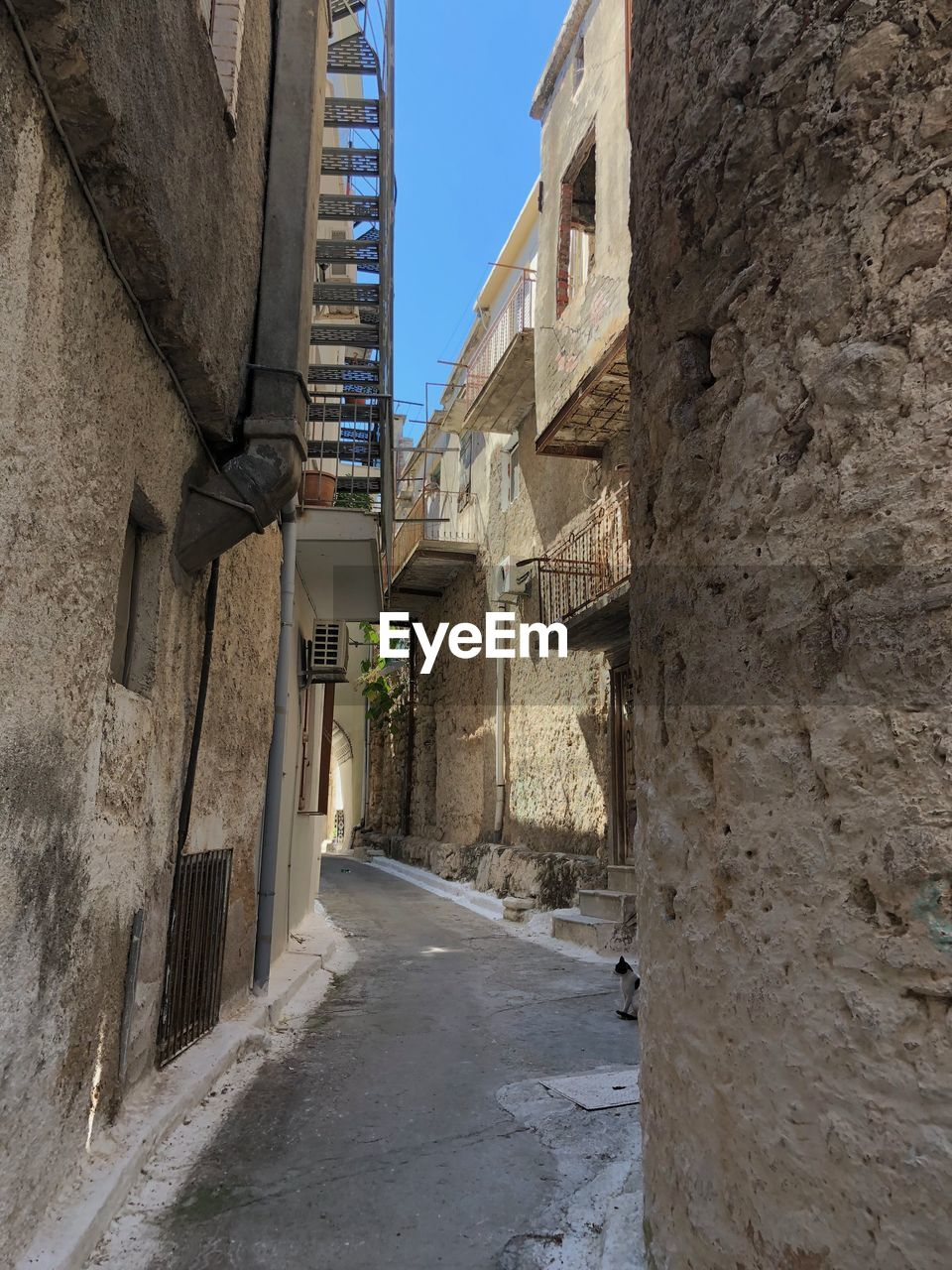 architecture, built structure, building exterior, building, direction, the way forward, wall - building feature, residential district, city, narrow, day, alley, no people, nature, wall, sky, outdoors, sunlight, street, footpath, stone wall, long