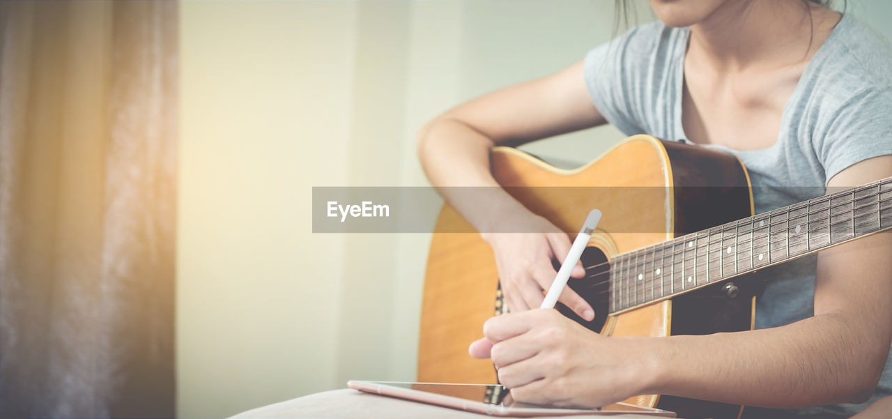 Midsection Of Woman With Guitar Sitting At Home