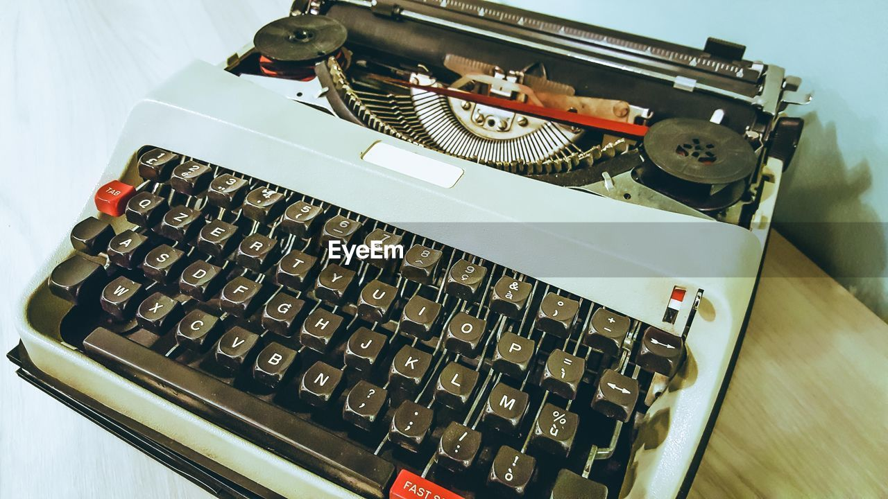 technology, high angle view, indoors, still life, typewriter, table, communication, close-up, retro styled, no people, focus on foreground, connection, number, letter, text, antique, alphabet, paper, old, blank
