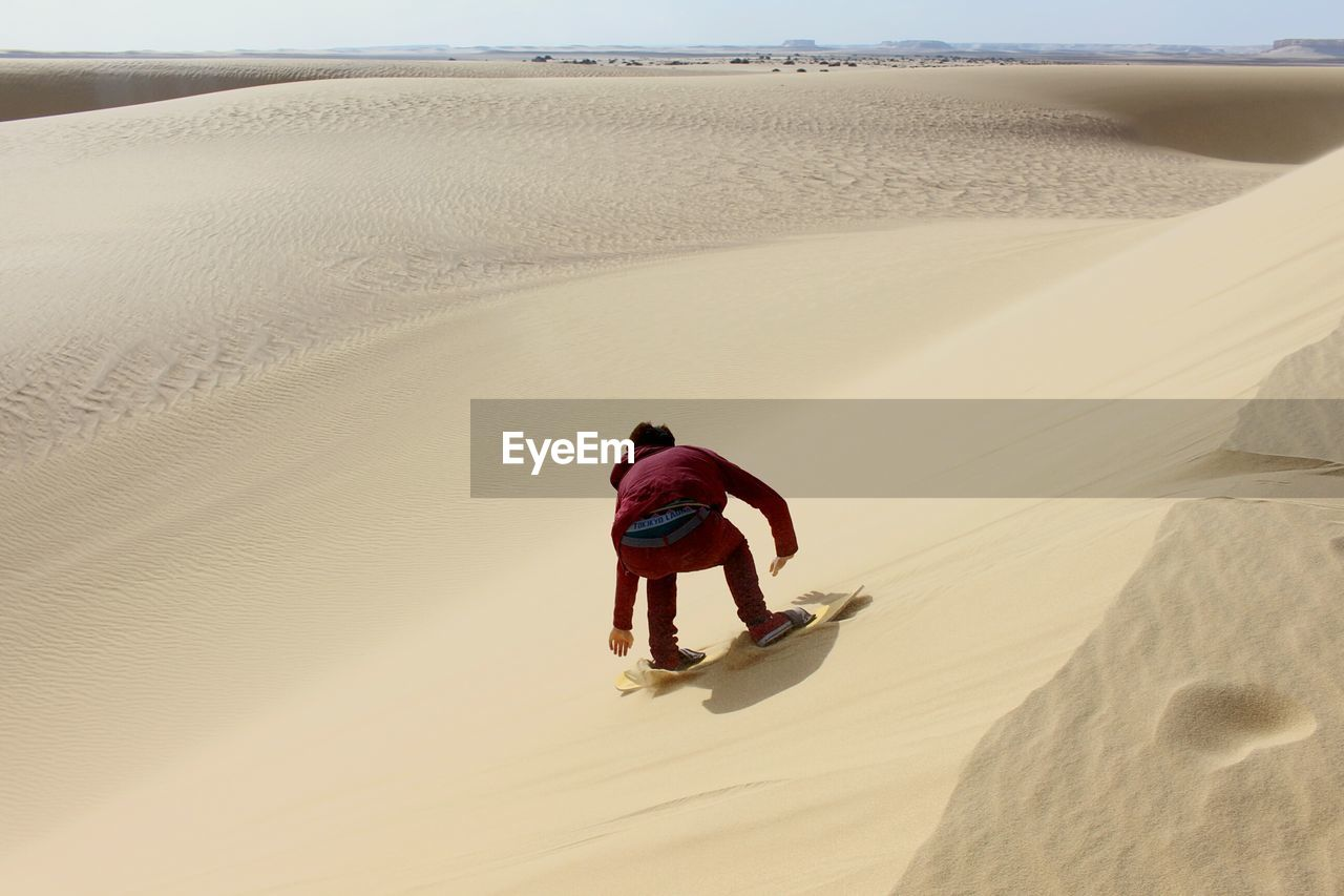 Rear view of man sandboarding