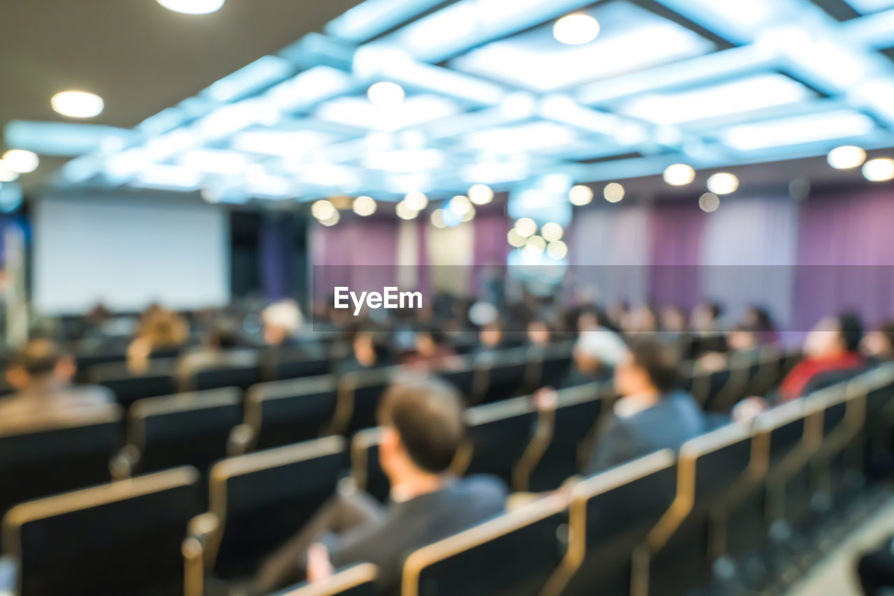 group of people, illuminated, real people, indoors, focus on foreground, lighting equipment, seat, people, business, men, crowd, incidental people, auditorium, light, adult, defocused, selective focus, group, women, stage, conference - event