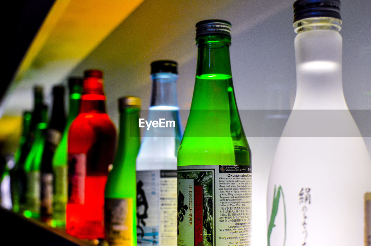 bottle, container, drink, refreshment, alcohol, food and drink, glass - material, indoors, no people, close-up, beer bottle, green color, transparent, still life, beer - alcohol, focus on foreground, table, choice, in a row, shelf