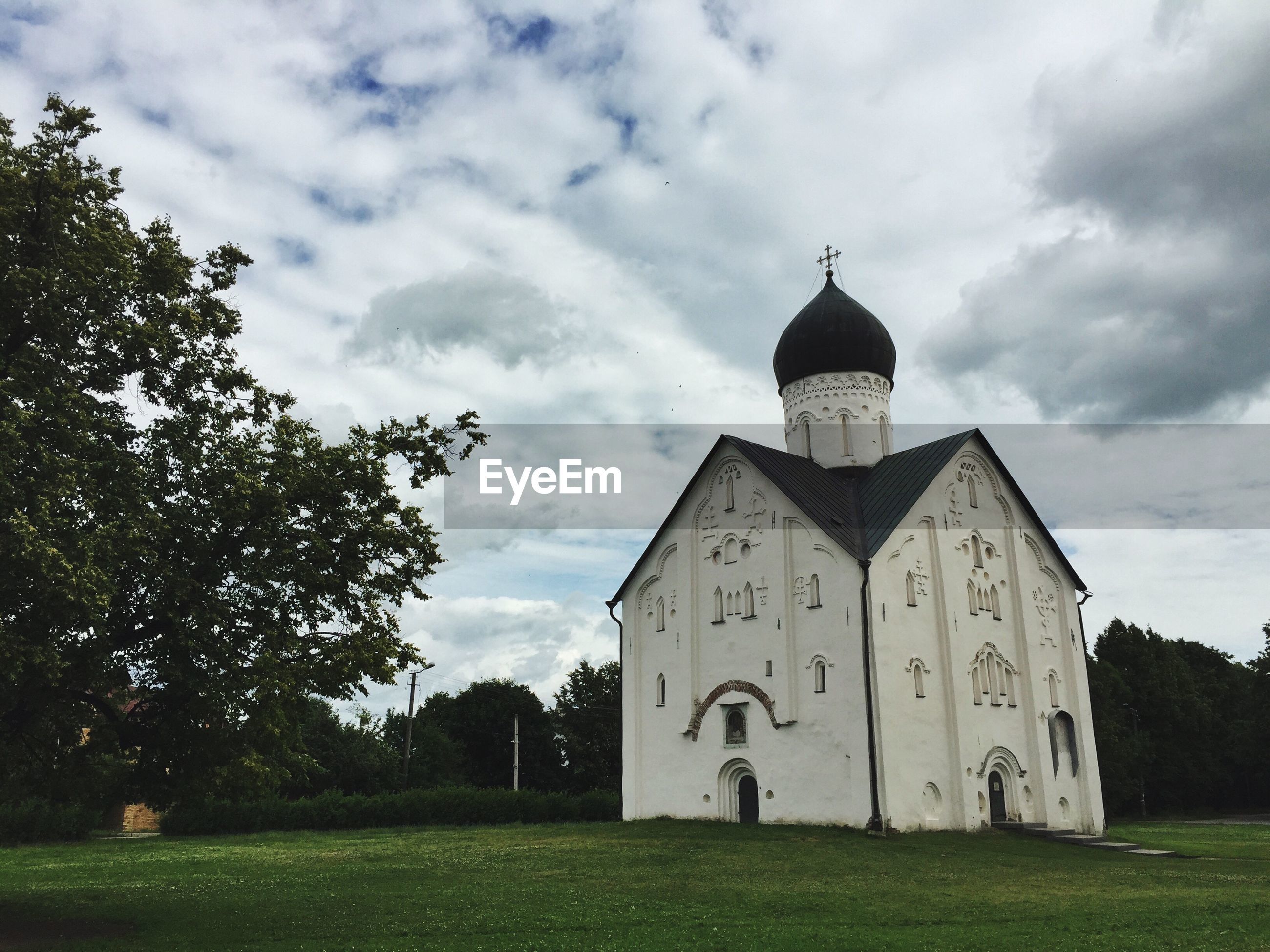 Low angle view of church against cloudy sky on grassy field