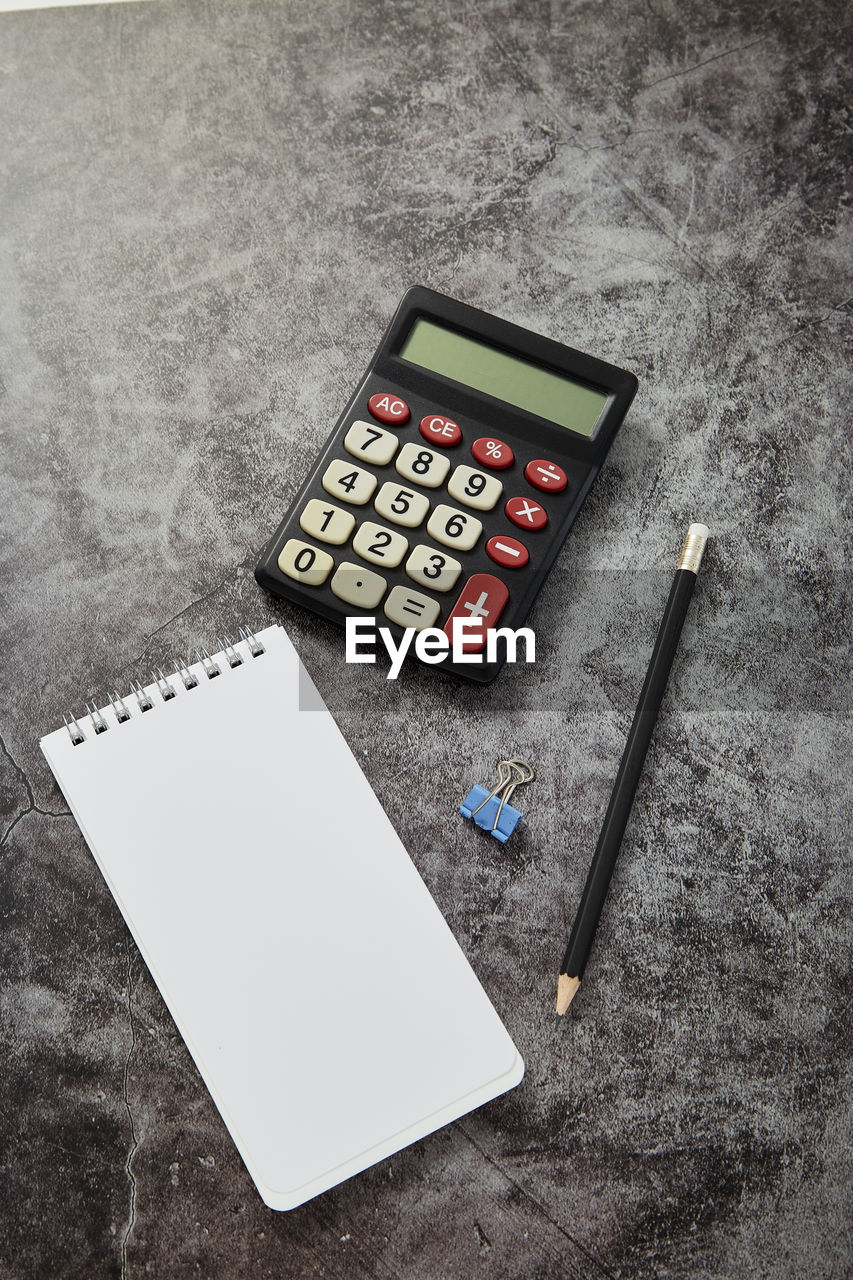 indoors, high angle view, table, no people, still life, calculator, close-up, number, finance, mathematics, technology, business, pencil, paper, communication, studio shot, pen, wood - material, directly above, accuracy, economy