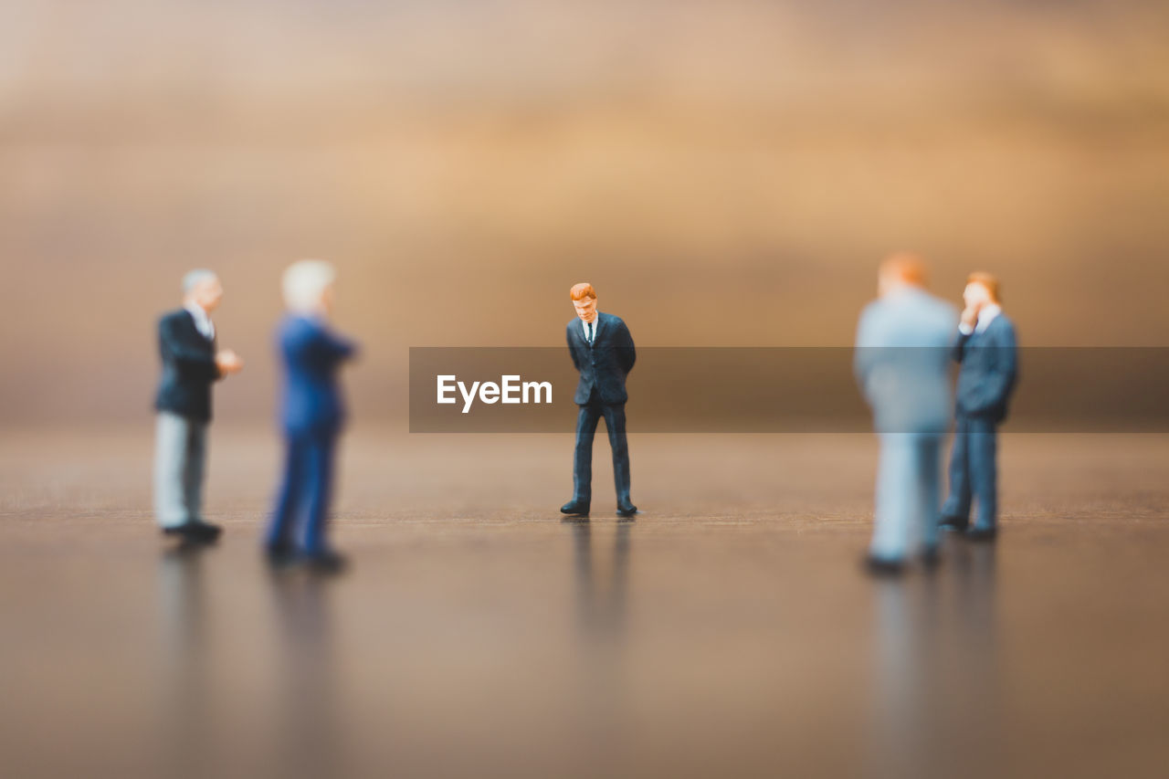 selective focus, men, figurine, group of people, human representation, table, people, male likeness, representation, standing, full length, cooperation, indoors, business, adult, day, teamwork, real people, competition, males