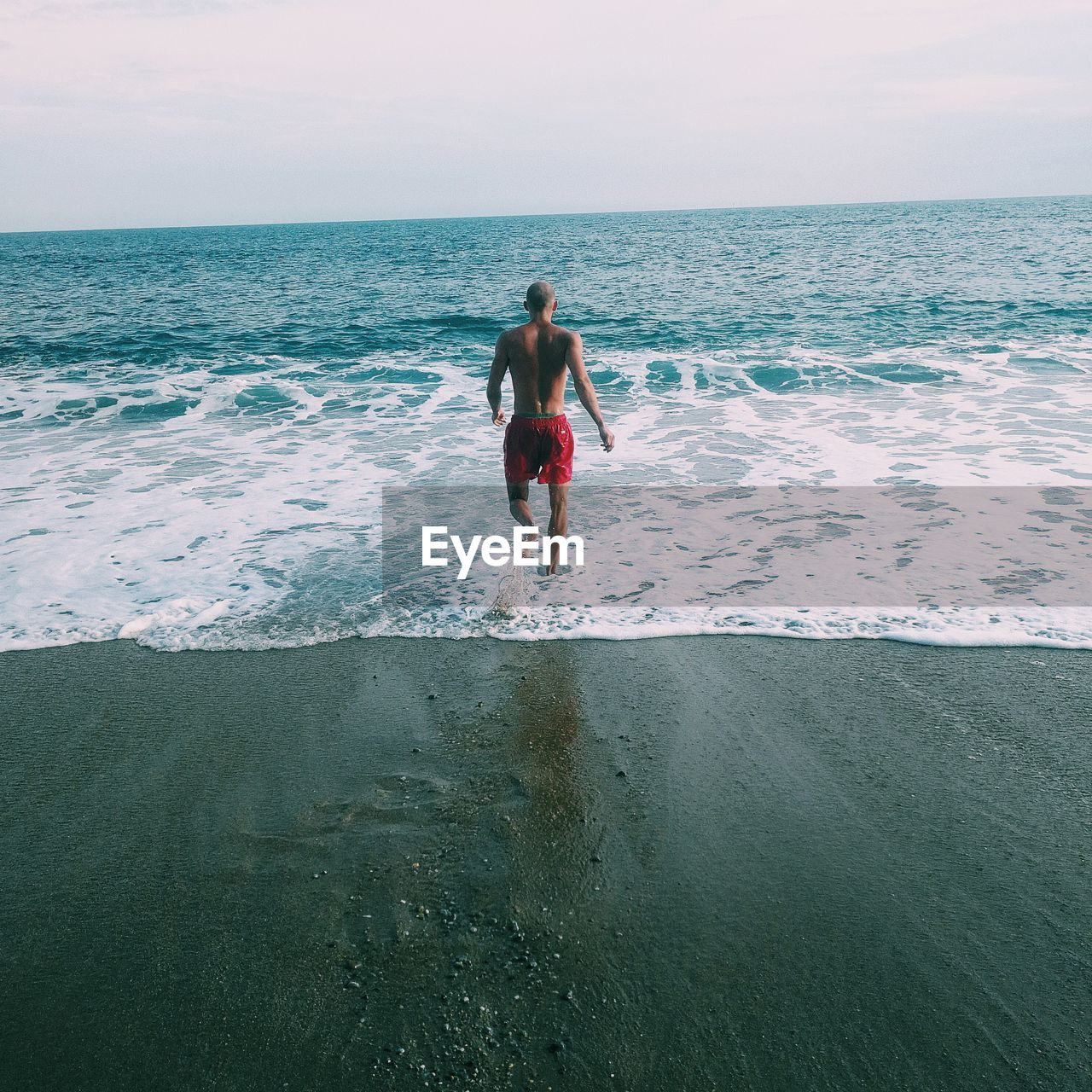 Rear View Of Shirtless Man Walking On Shore At Beach Against Sky