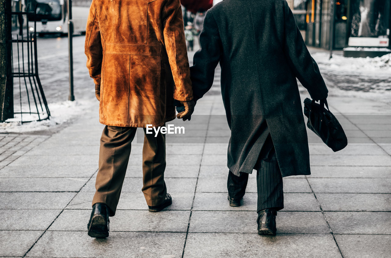Low Section Of Men Walking On Street