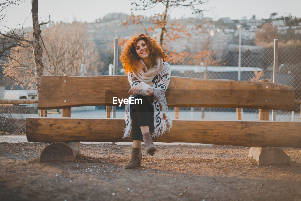 Full Length Of Smiling Young Woman Sitting On Bench