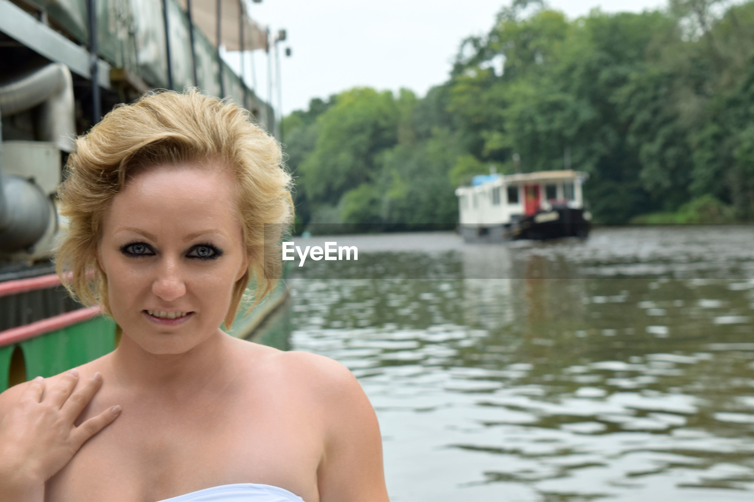 PORTRAIT OF YOUNG WOMAN IN BOAT AGAINST BLURRED BACKGROUND