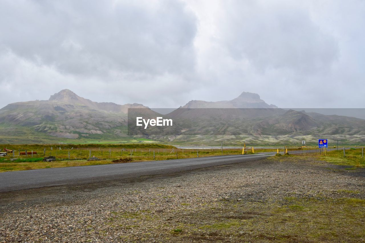 mountain, road, sky, transportation, cloud - sky, scenics - nature, beauty in nature, environment, nature, tranquil scene, tranquility, mountain range, the way forward, direction, day, non-urban scene, landscape, no people, sign, land, outdoors, long