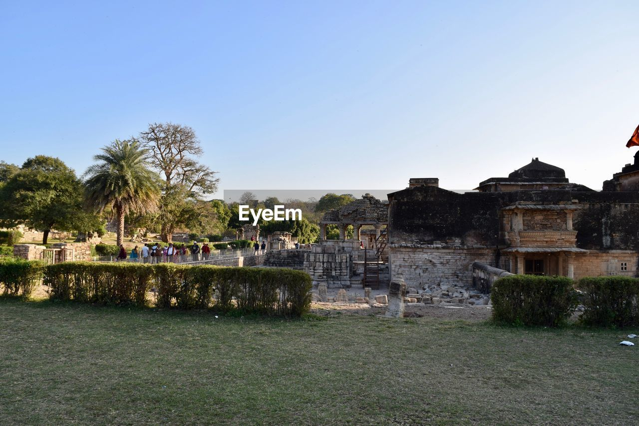 architecture, built structure, building exterior, old ruin, tree, clear sky, travel destinations, outdoors, day, palm tree, water, no people, sky, nature, ancient civilization