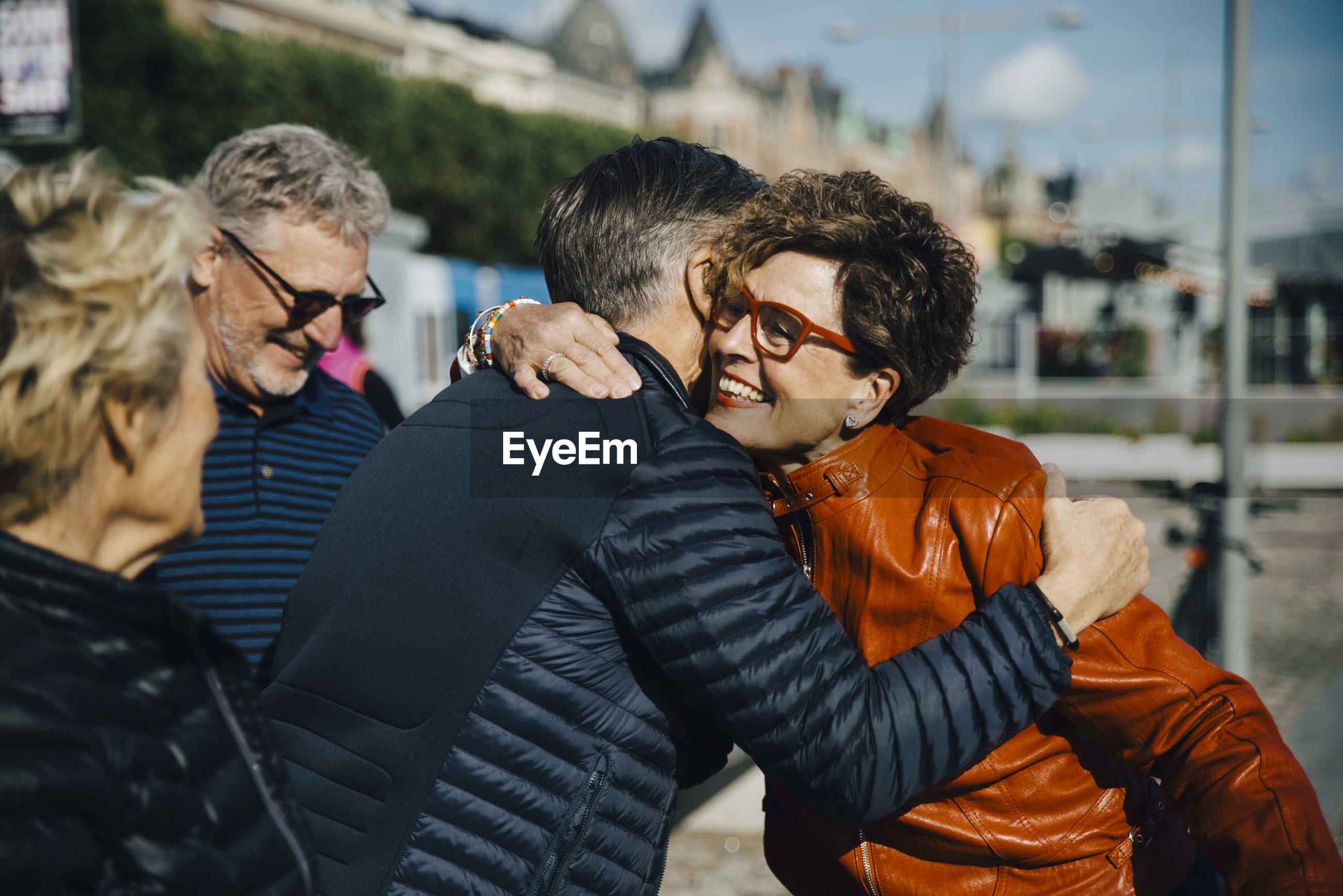 Happy senior woman embracing man by friends in city during vacation