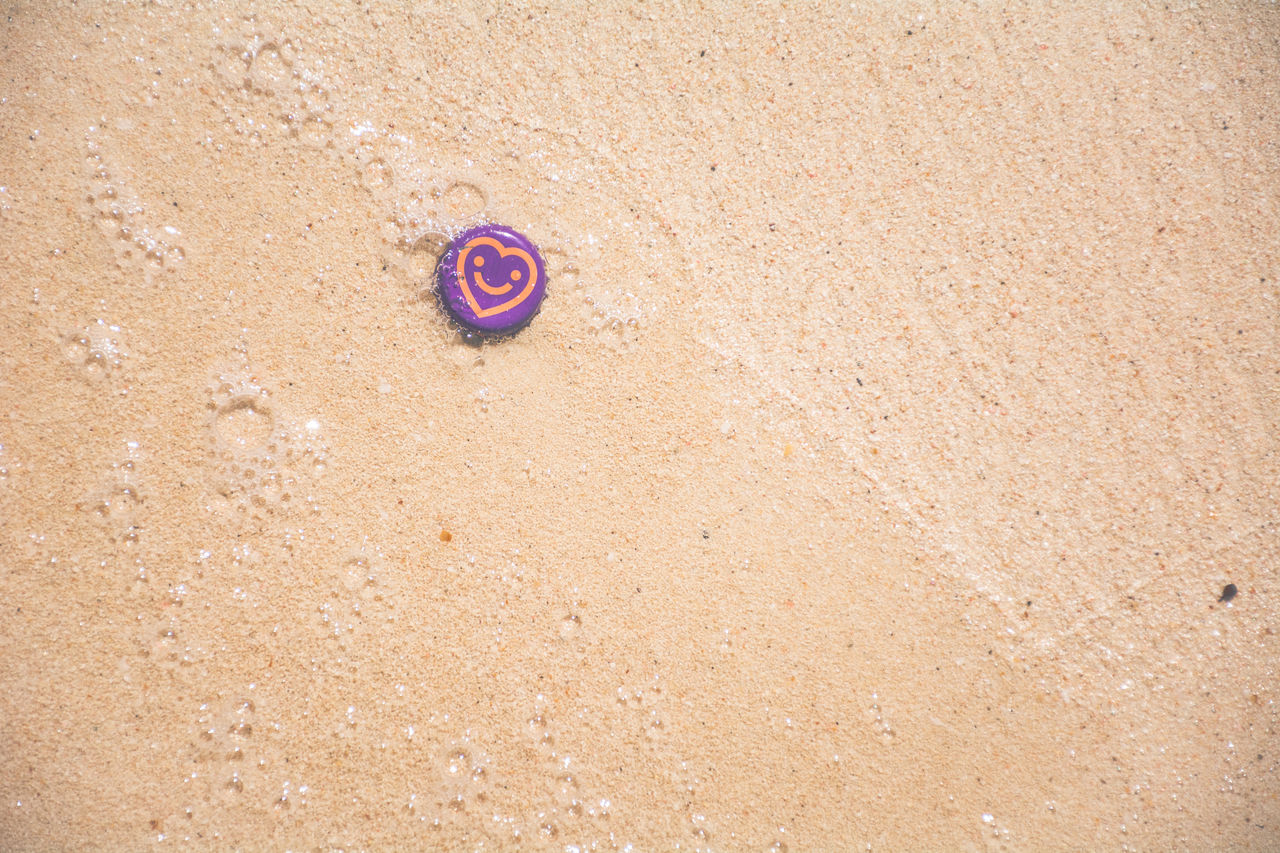 High angle view of bottle cap on sand at beach