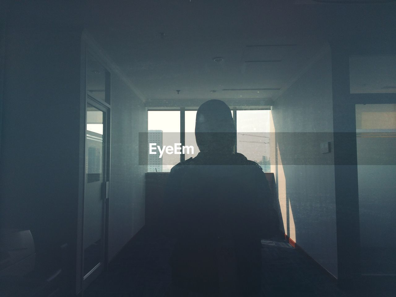 one person, window, rear view, real people, indoors, architecture, standing, day, built structure, lifestyles, men, dark, building, silhouette, waist up, transparent, leisure activity, sunlight