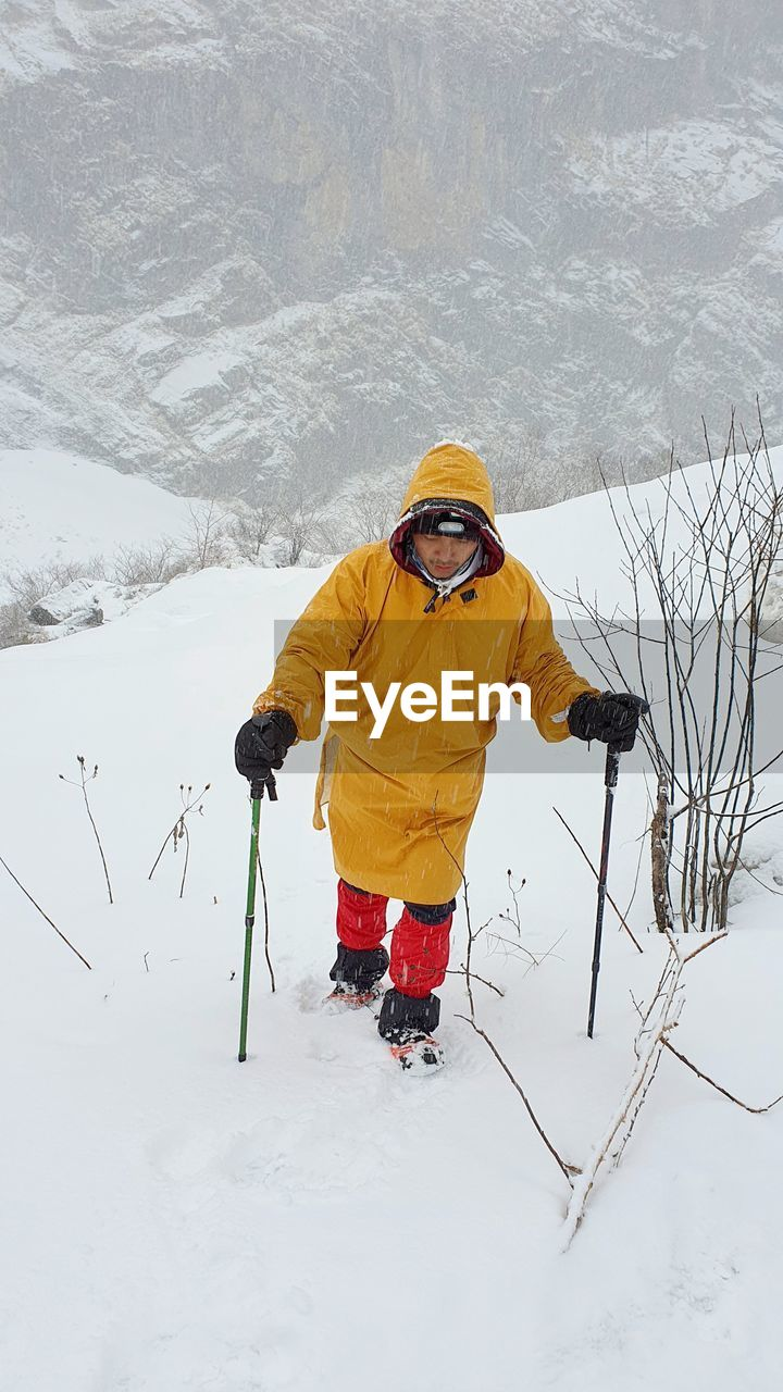 WOMAN WITH UMBRELLA ON SNOW COVERED FIELD AGAINST MOUNTAIN