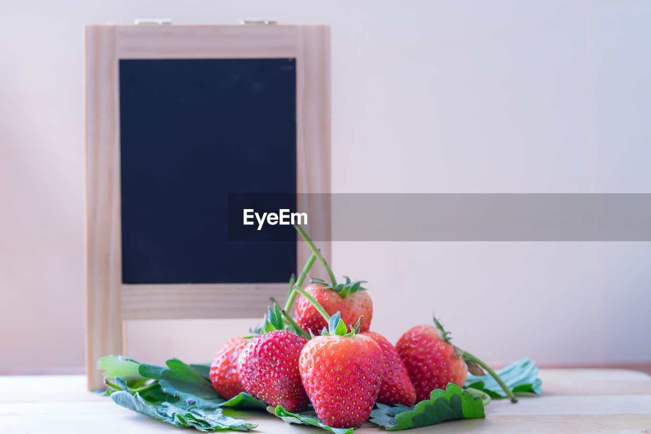 food and drink, healthy eating, food, fruit, freshness, still life, wellbeing, table, berry fruit, no people, indoors, strawberry, close-up, focus on foreground, red, copy space, day, green color, ripe, wood - material