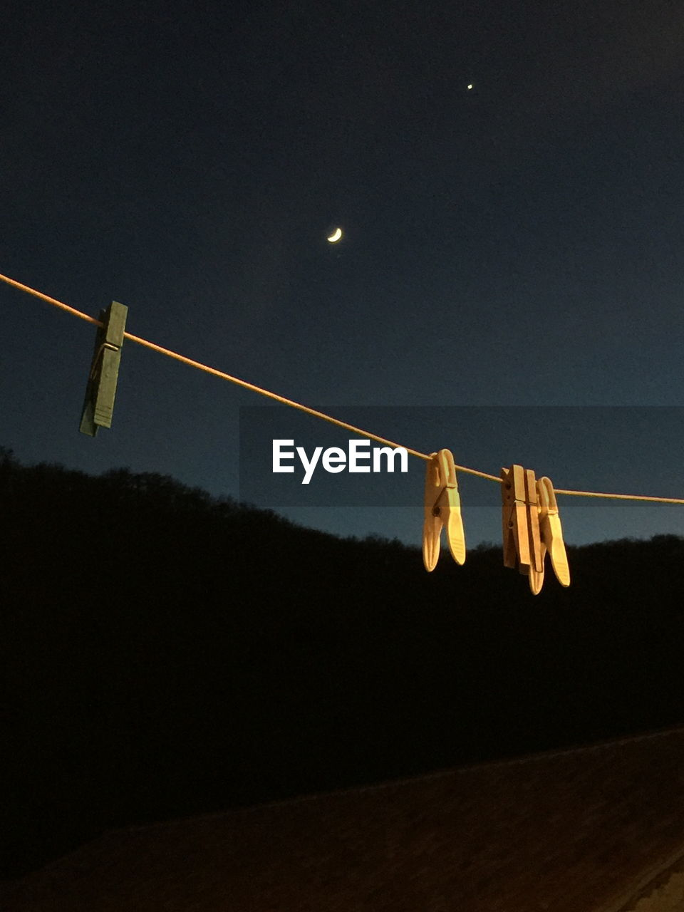 Low Angle View Of Clothespin Hanging On Rope Against Sky At Night