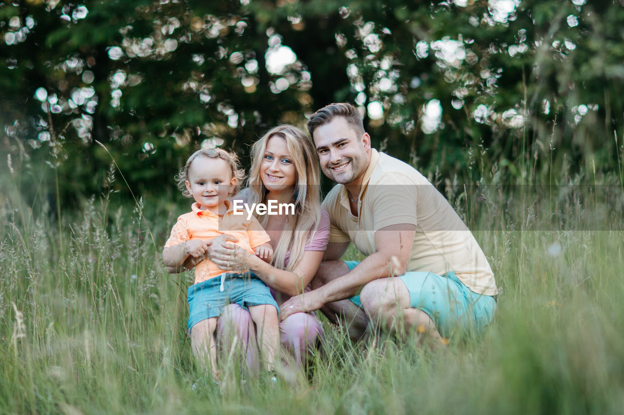 Portrait Of Smiling Family On Field At Park