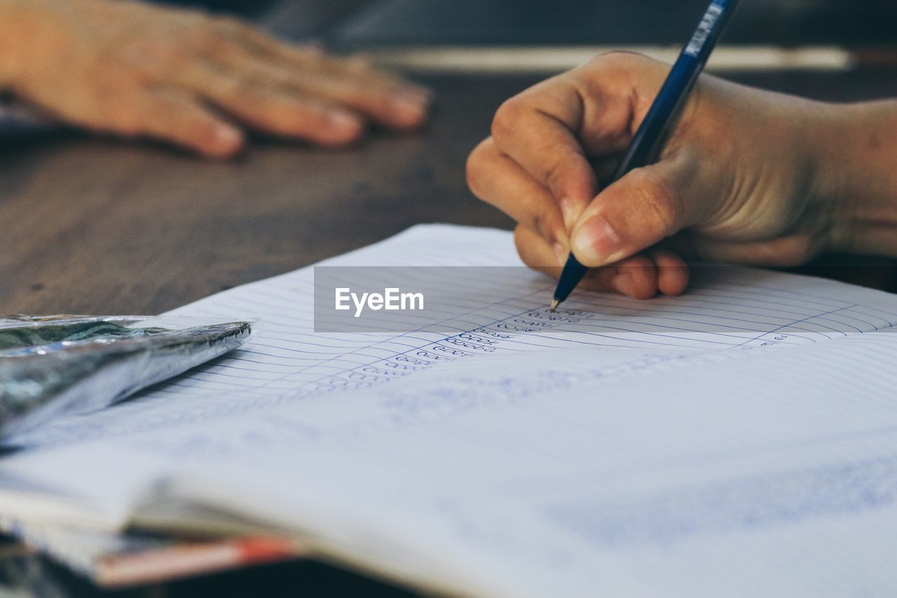 Cropped hand writing in book at table