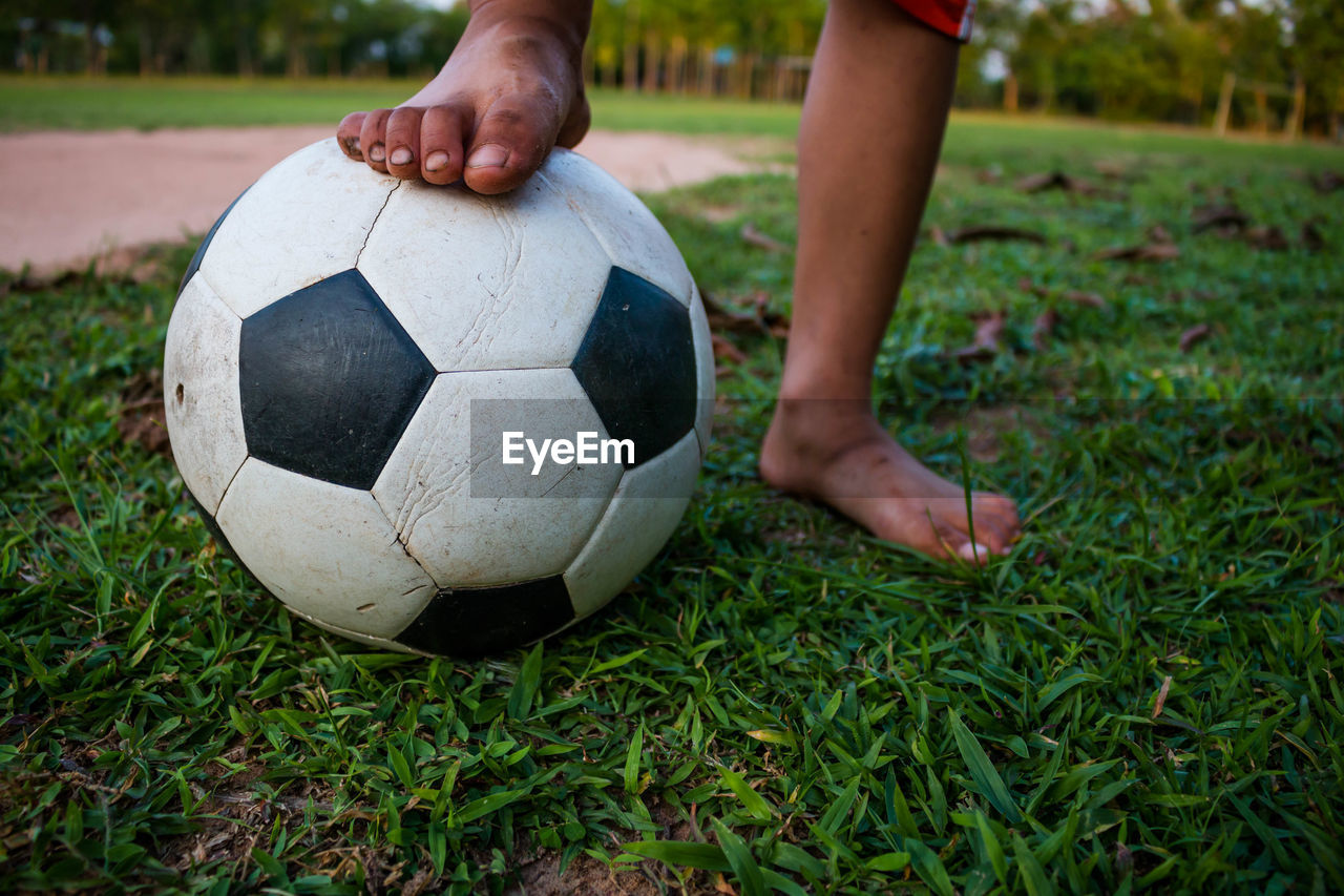 Low Section Of Child Playing Soccer On Grass