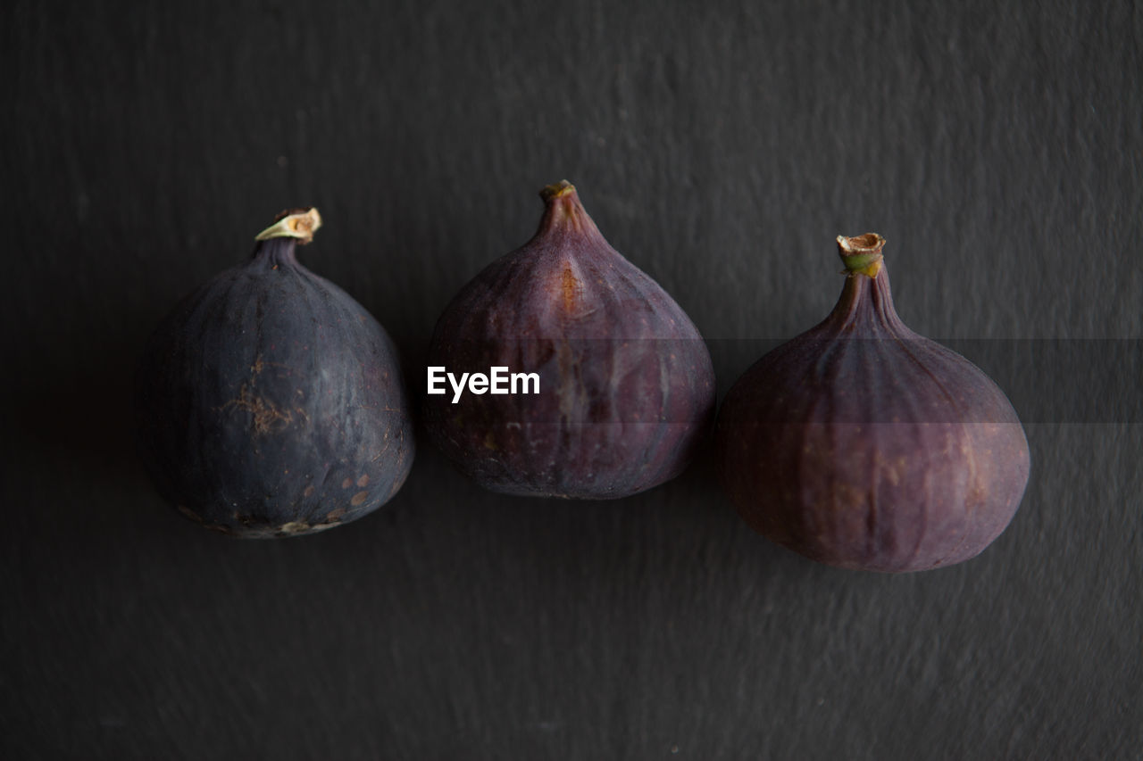 food and drink, still life, food, wellbeing, freshness, no people, healthy eating, indoors, table, close-up, fig, group of objects, fruit, three objects, studio shot, side by side, raw food, vegetable, wood - material, five objects, black background, purple