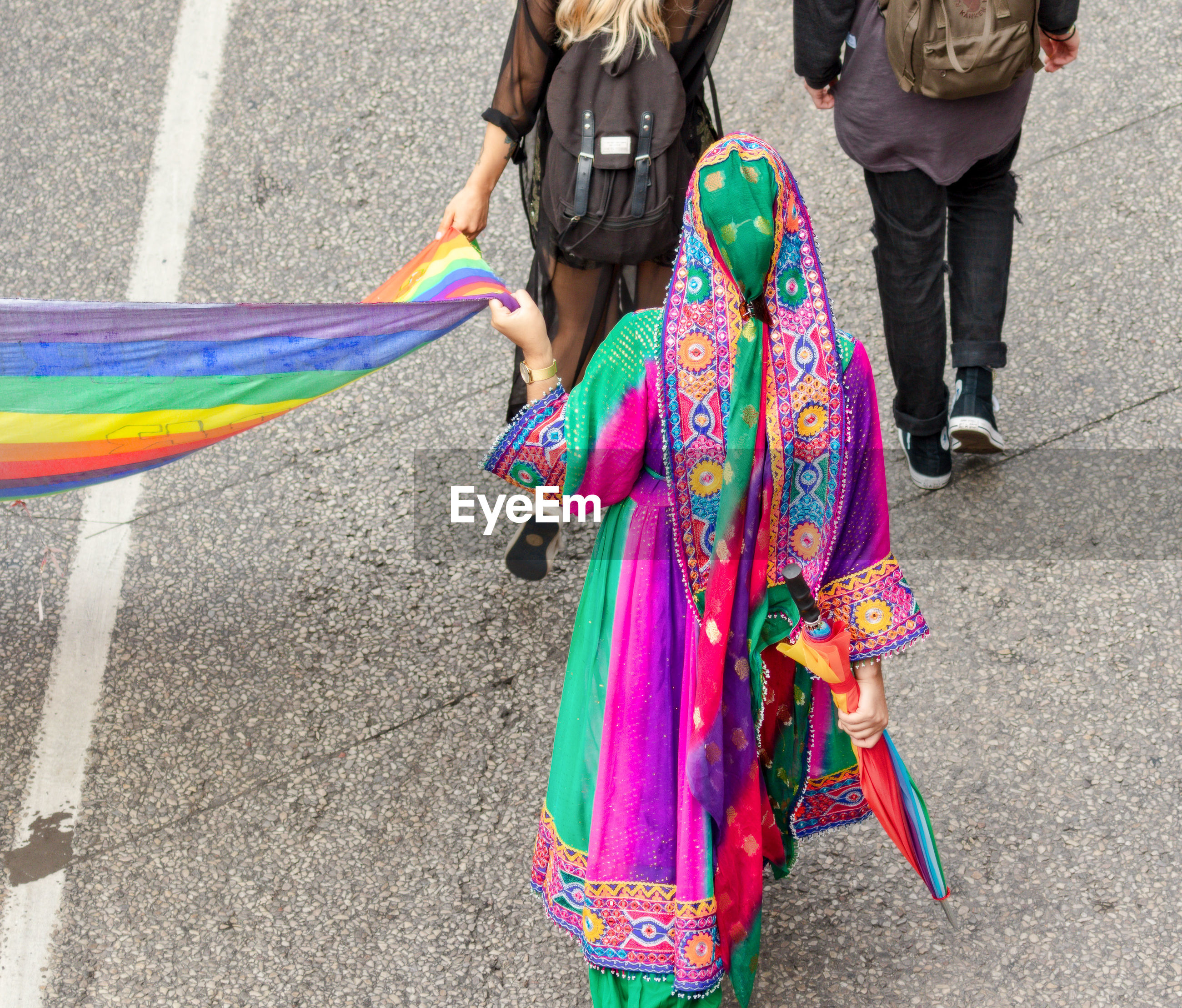High angle view of women holding rainbow flag while walking on footpath