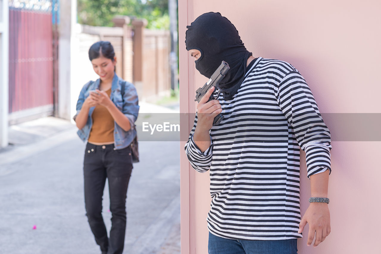 Thief with gun hiding against wall by smiling young woman walking on street by