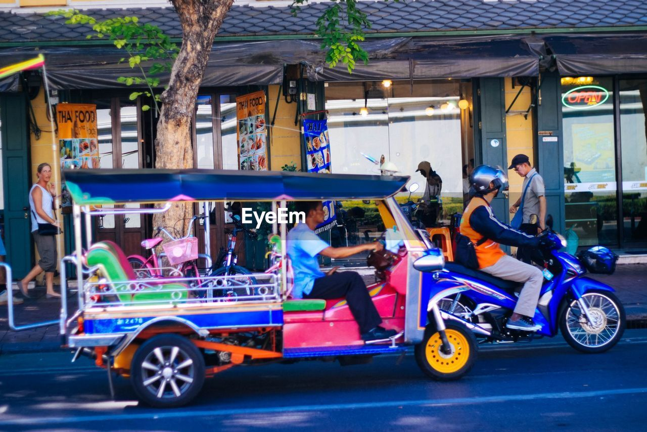 transportation, mode of transport, land vehicle, motorcycle, riding, men, outdoors, real people, bicycle, day, group of people, multi colored, building exterior, architecture, city, adult, people