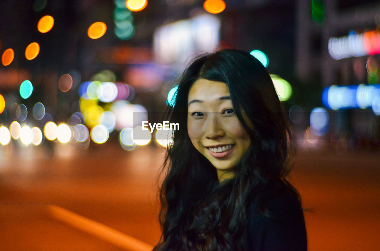 Portrait Of Happy Woman In City At Night