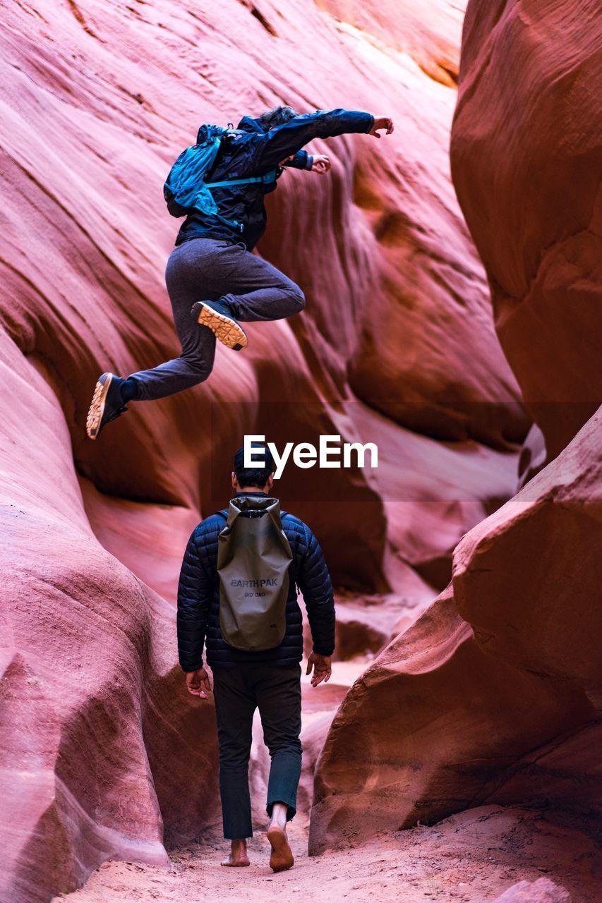 Man Jumping Over Friend At Canyon