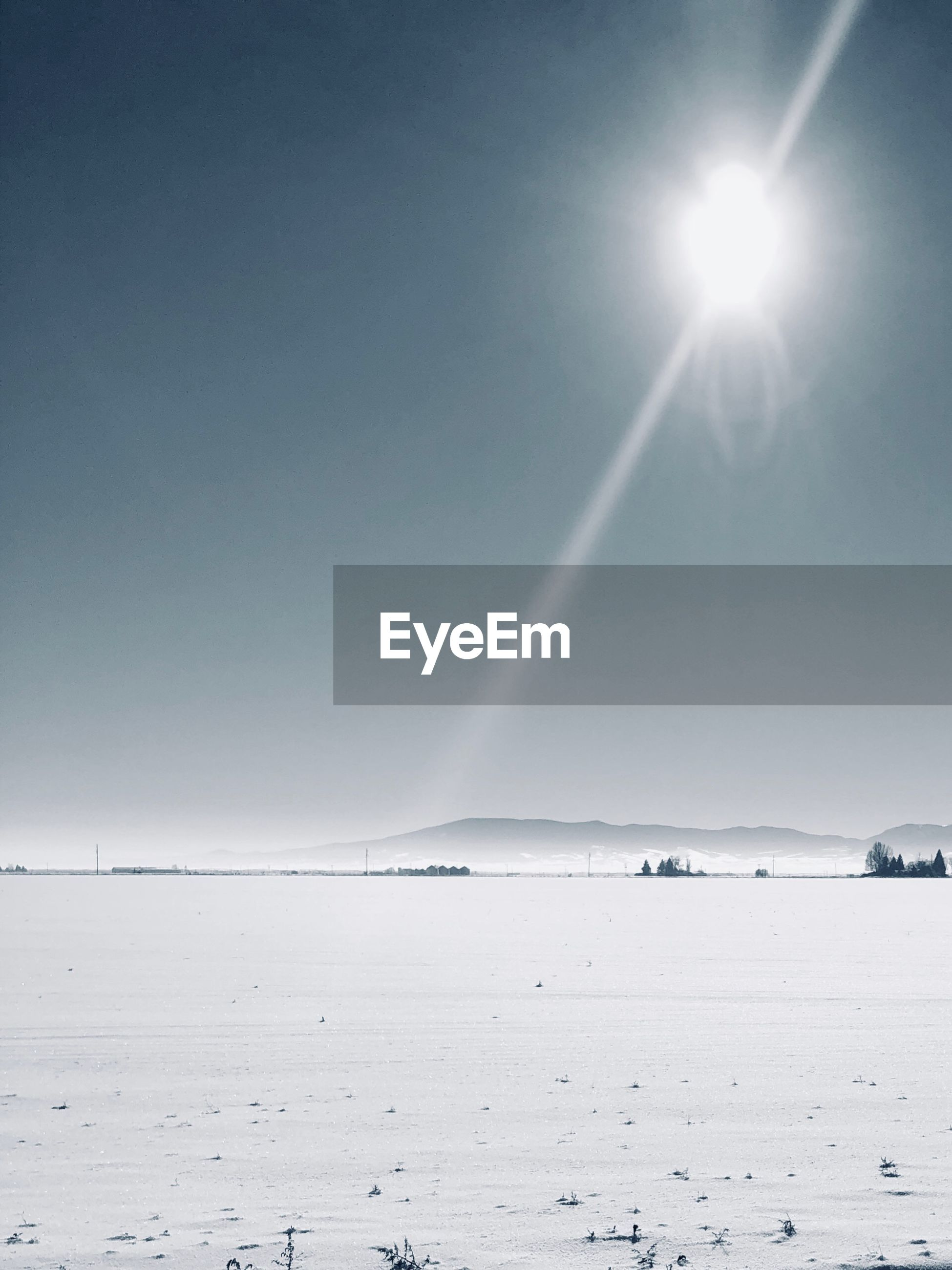 SCENIC VIEW OF SNOW COVERED LAND AGAINST BRIGHT SUN IN SKY