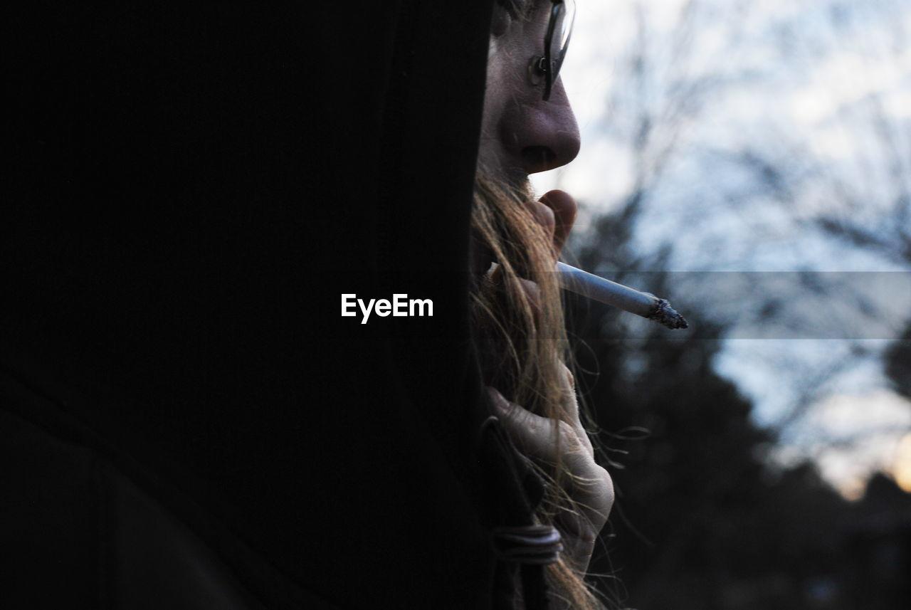 Close-up of man smoking cigarette against sky