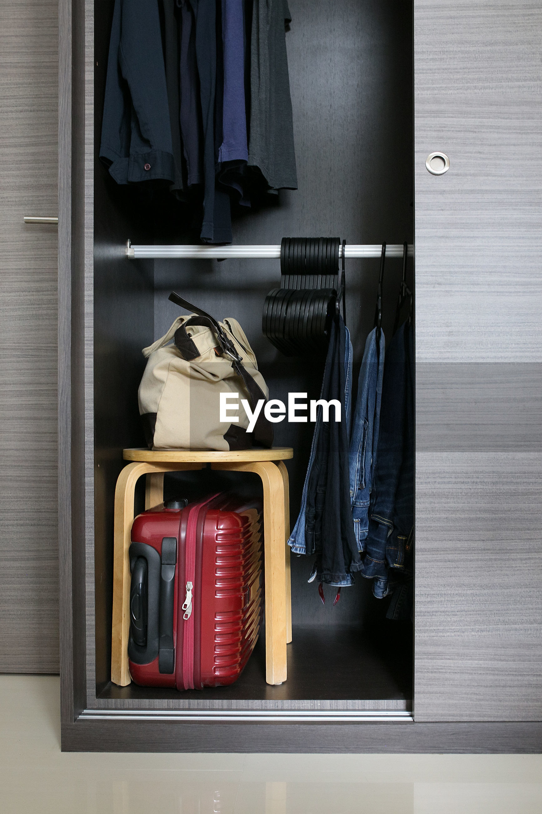 Luggage with stool and clothing in cabinet