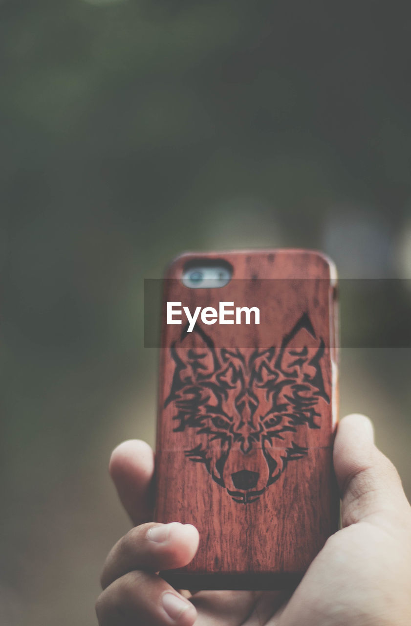 Close-up of cropped hand holding mobile phone cover with animal print