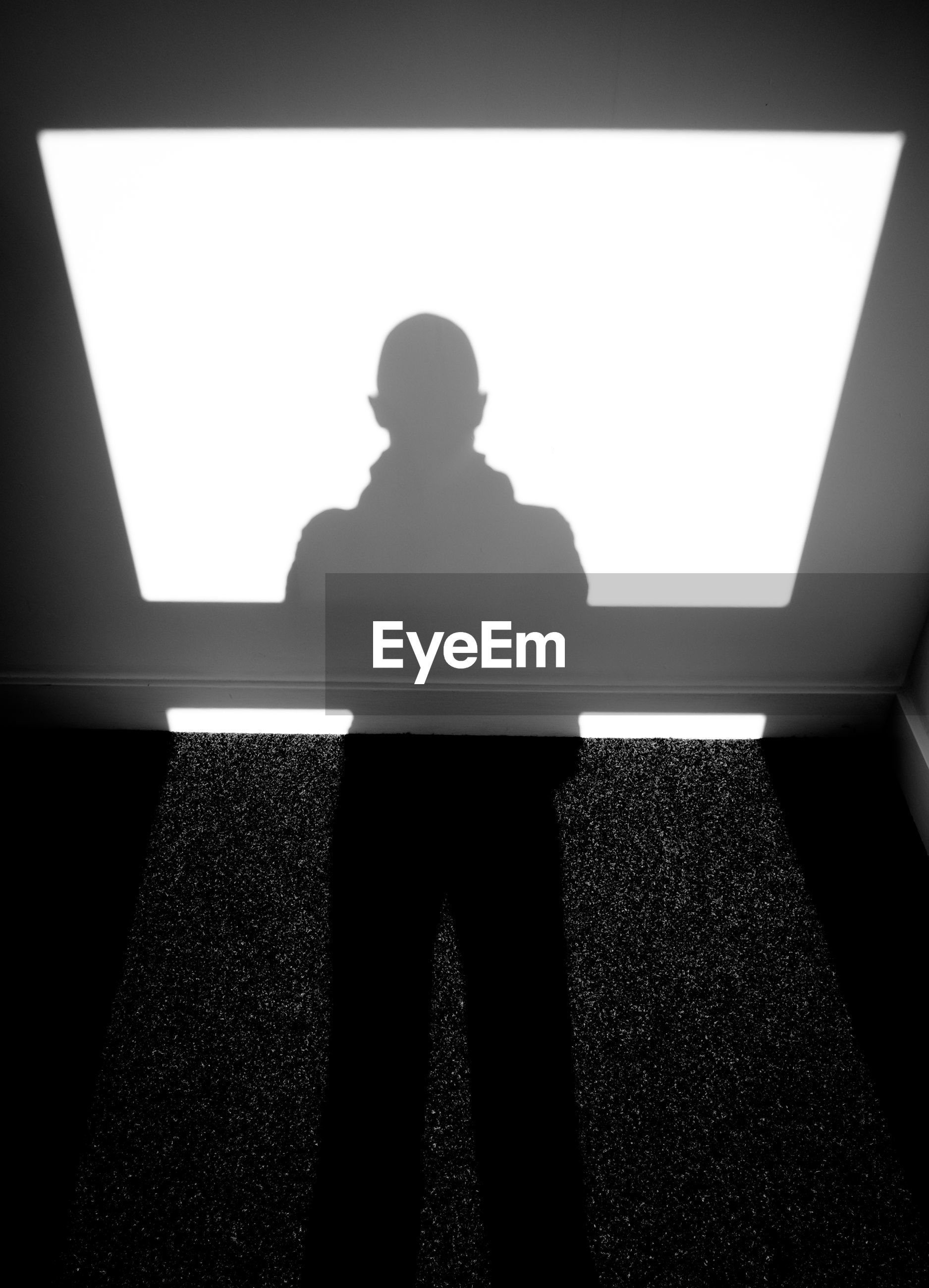 REAR VIEW OF SILHOUETTE MAN STANDING AGAINST ILLUMINATED WINDOW