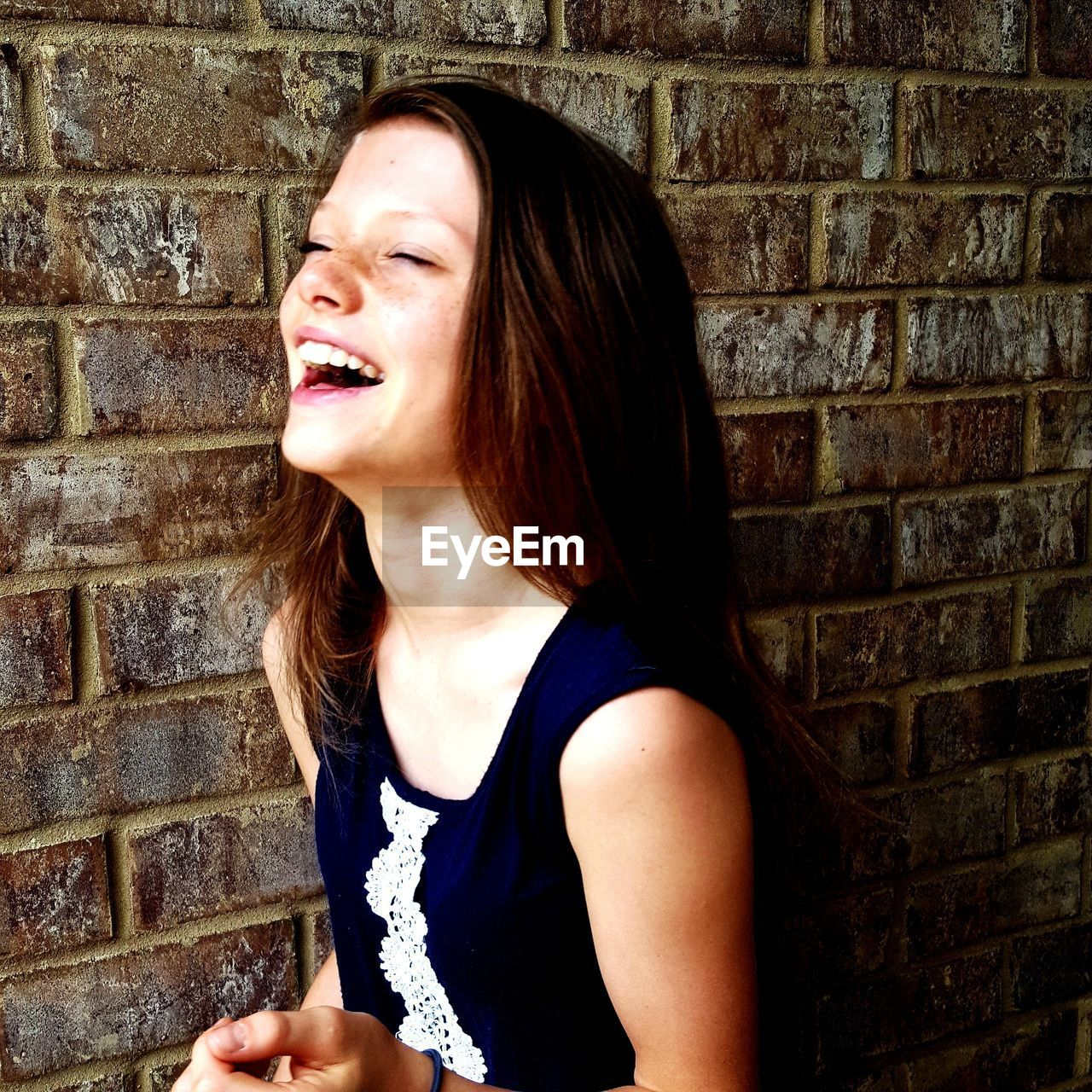Cheerful girl standing against brick wall