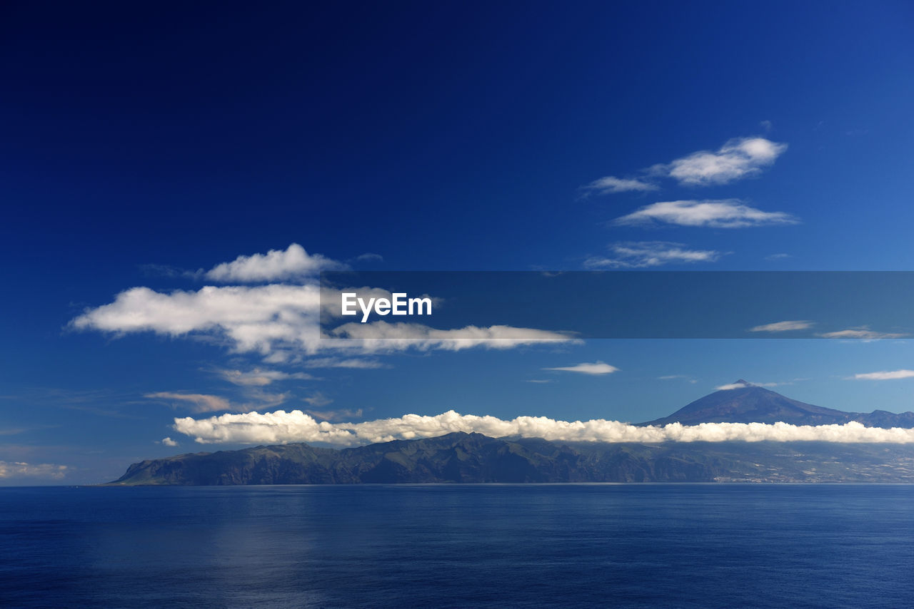 Scenic view of clouds over sea by mountain against blue sky