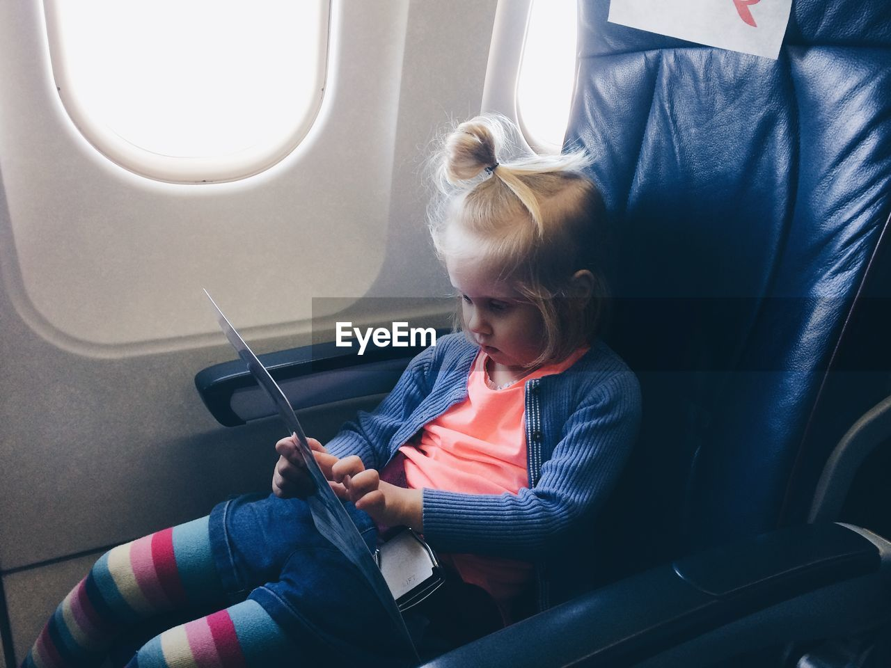 Girl reading chart while sitting by window in airplane