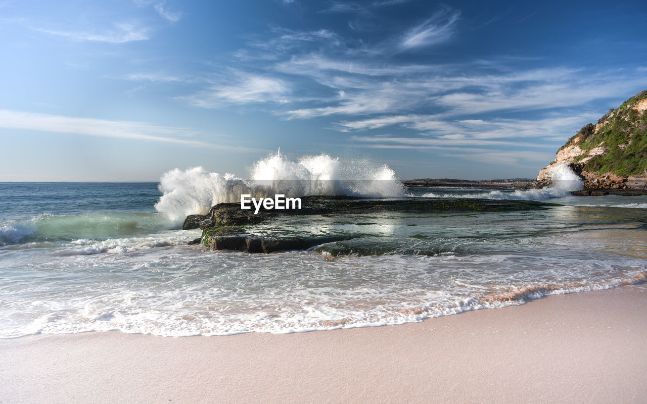 Wave - waters splashing on rocks on shore at beach against blue sky