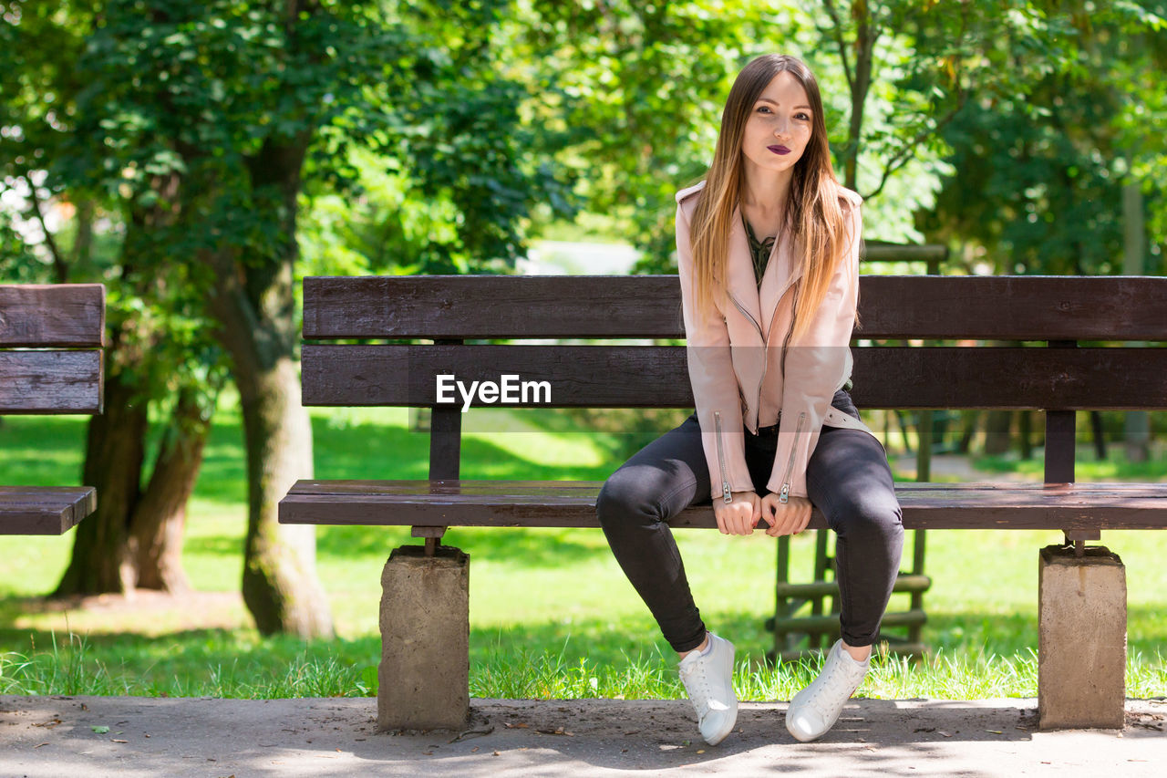 Full length portrait of beautiful woman relaxing on bench at park during sunny day