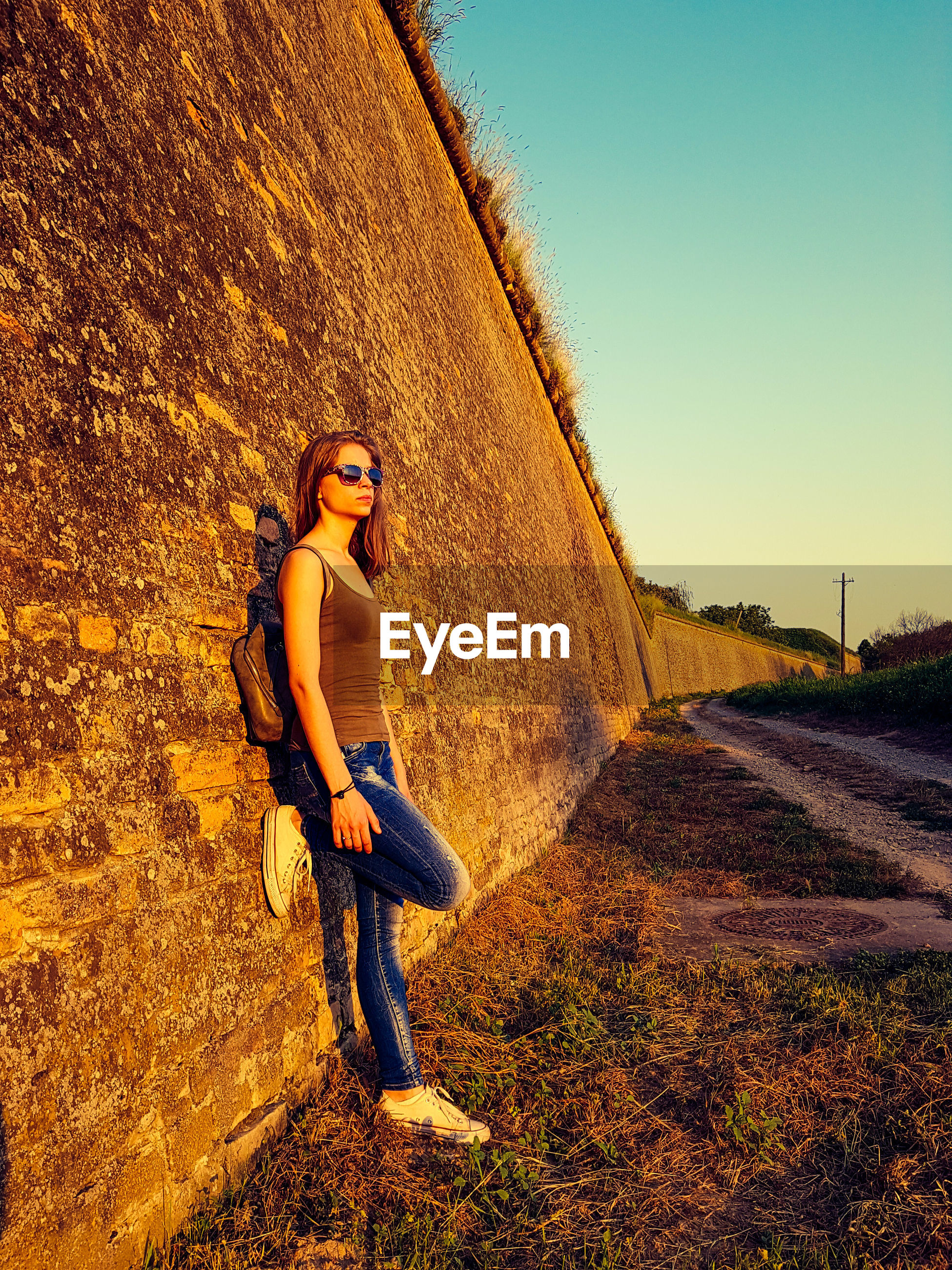 Side view of young woman standing on field by retaining wall against clear sky during sunset
