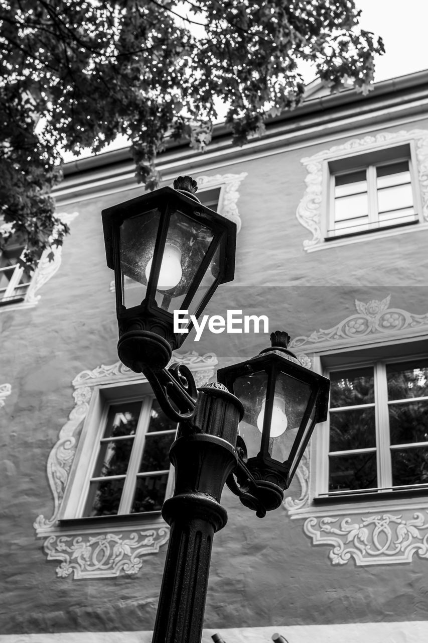 lighting equipment, low angle view, communication, tree, building exterior, outdoors, street light, no people, built structure, architecture, day, technology, close-up