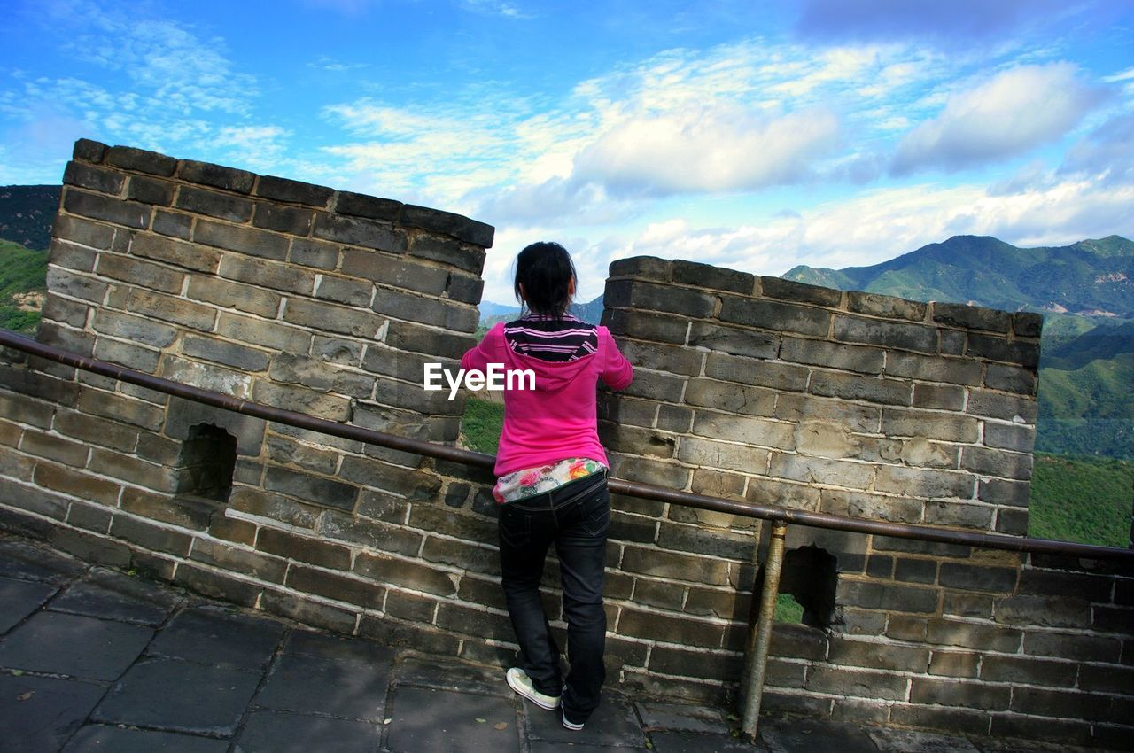 Woman standing on great wall of china against sky